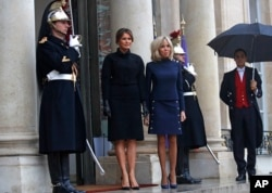 France's first lady Brigitte Macron, center-right, and her U.S. counterpart Melania Trump, center-left, stand on the steps of the Elysee Palace in Paris, France, Nov.10, 2018.