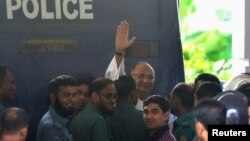 FILE - Salahuddin Quader Chowdhury, a senior opposition leader, waves to the media after he arrives at the war crime tribunal, in Dhaka, Bangladesh, Oct. 1, 2013.