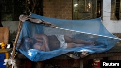 A laborer sleeps under a mosquito net on a hot summer morning in New Delhi