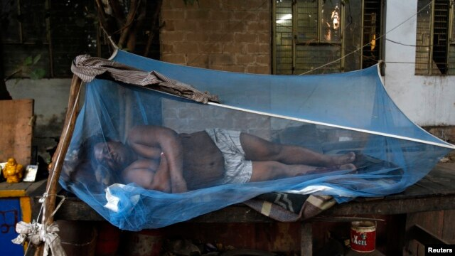 Laborer sleeps on a makeshift bed covered with a mosquito net on a hot summer morning, New Delhi, May 23, 2013.