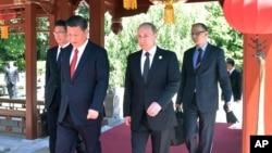 """在北京的 """"一帶一路""""國際合作高峰論壇開幕式前,中國主席習近平和俄羅斯總統普京走在一起(2017年5月14日)"""