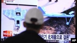 Seorang pria melihat TV yang memperlihatkan kapal tanpa awak yang dituduh Korea Selatan sebagai pesawat mata-mata Korea Utara (2/4/2014).
