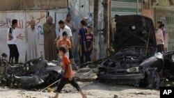 Warga Irak memeriksa lokasi pemboman bunuh diri di distrik Husseiniyah, Baghdad (25/6).