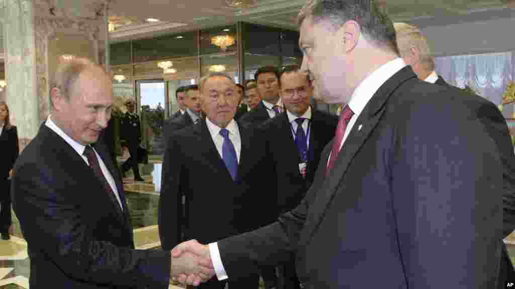 Russian President Vladimir Putin, left, shakes hands with Ukrainian President Petro Poroshenko as Kazakh President Nursultan Nazarbayev looks on prior to their talks in Minsk, Belarus, Aug. 26, 2014.