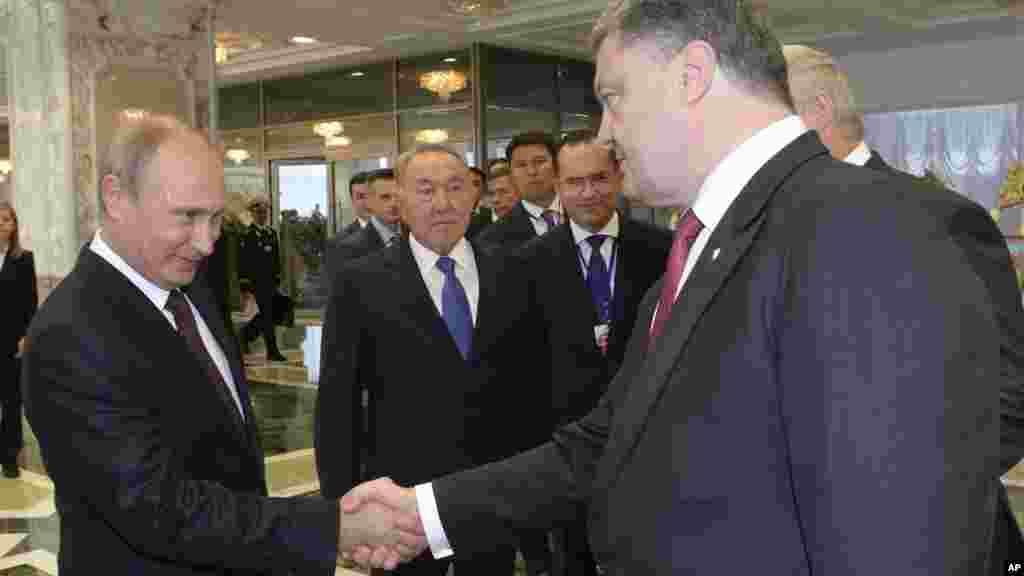 Russian President Vladimir Putin, left, shakes hands with Ukrainian President Petro Poroshenko as Kazakh President Nursultan Nazarbayev looks on prior to their talks in Minsk, Belarus, Aug. 26, 2014.