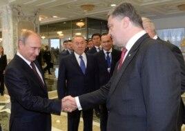 Russian President Vladimir Putin shakes hands with Ukrainian President Petro Poroshenko as Kazakh President Nursultan Nazarbayev looks on prior to their talks in Minsk, Belarus, Aug. 26, 2014.