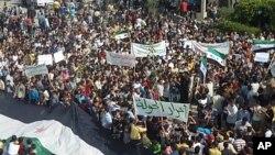 Xwenîşanderên demokrasîxwaz li Hula ya nêzîkî bajarê Himusê Beşar Esed protesto dikin. Cotmeh, 27, 2011.