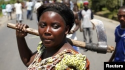 A female protester holds an axe during a protest against Burundian President Pierre Nkurunziza's decision to run for a third term in Bujumbura, Burundi, May 13, 2015.