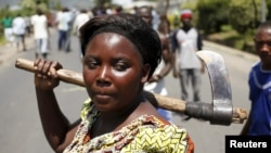 A female protester holds an ax during a protest against Burundian President Pierre Nkurunziza's decision to run for a third term in Bujumbura, Burundi, May 13, 2015.