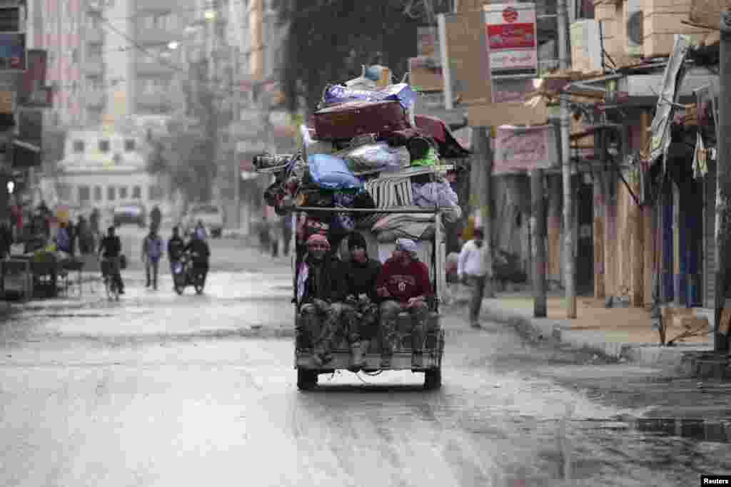 Free Syrian Army fighters sit on the back of a pick-up truck in the Mouazafeen neighbourhood in Deir al-Zor, Nov. 10, 2013.