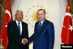 FILE - Turkey's President Tayyip Erdogan (R) shakes hands with Secretary General of the Council of Europe Thorbjorn Jagland before a meeting at the Presidential Palace in Ankara, Turkey, Aug. 3, 2016.