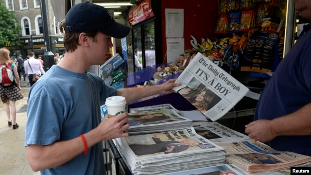 A man buys a newspaper displaying the news of the Royal birth by Britain's Catherine, Duchess of Cambridge in central London, July 23, 2013. Already touted as one of the most famous babies in the world, the first child of Prince William and wife Kate face