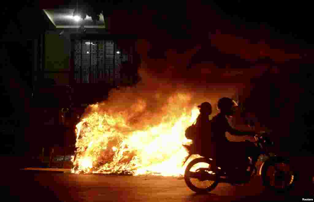 "A motorcycles passes a bonfire during a protest by members of the ""Free Pass"" movement to demand zero tariffs in the Brazilian public transport system in Rio de Janeiro, Feb. 6, 2014."