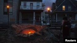 Seorang warga Queens, Shane Decarolis, berdiri di dekat perapian di luar rumahnya (3/11). Sebagian listrik di wilayah New York, termasuk Queens dan Staten Island, hingga kini masih belum mendapat aliran listrik pasca hantaman badai Sandy.