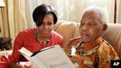 Ibu negara AS, Michelle Obama (kiri) saat berkunjung ke kediaman almarhum Nelson Mandela di Houghton, Afrika Selatan (foto: dok).