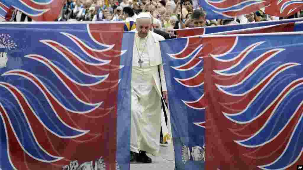 Le pape François est encadré par des drapeaux traditionnels d'une délégation de fidèles de Carovigno, du Sud de l'Italie, à son arrivée à la place Saint-Pierre pour assister à l'audience générale hebdomadaire au Vatican, le 15 octobre 2014 (AP Photo / Gregorio Borgia)