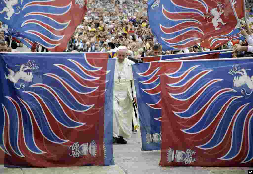 Pope Francis is framed by traditional flags from a delegation of faithful from Carovigno, southern Italy, as he arrives in St. Peter's Square to attend the weekly general audience, at the Vatican.