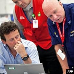 英国石油公司负责人和海岸警卫队员讨论截堵漏油