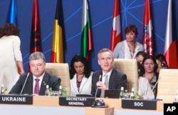 FILE - NATO Secretary General Jens Stoltenberg, right, and Ukraine's President Petro Poroshenko attend a working session of the NATO-Ukraine Commission at the NATO summit in Warsaw, Poland, July 9, 2016.