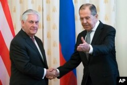 FILE - U.S. Secretary of State Rex Tillerson and Russian Foreign Minister Sergey Lavrov shake hands prior to their talks in Moscow, Russia, April 12, 2017.