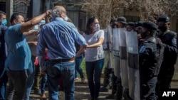 El periodista nicaragüense Carlos Fernando Chamorro, director de las publicaciones Confidencial y Esta Semana, es empujado por la policía antidisturbios frente a las oficinas de Confidencial en Managua, el 14 de diciembre de 2020.