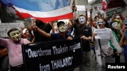Protesters wearing masks shout slogans as they march though Bangkok's shopping district, June 2, 2013.