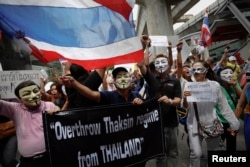 Para demonstran menggunakan topeng sambil meneriakkan slogan-slogan di distrik pertokoan Bangkok (2/6).