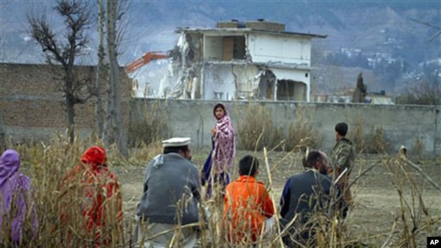 A Pakistan family watches the destruction of Osama bin Laden's compound in Abbottabad, Pakistan, February 26, 2012.