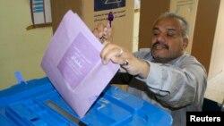 Glasač ubacuje svoj glasački listić i pokazuje prst označen mastilom na glasačkom mestu u Bagdadu