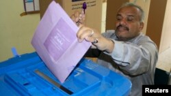 A man holds up his ink-stained finger as he casts his vote at a polling station in Baghdad, April 20, 2013.