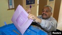 Seorang peserta pemilu memamerkan jarinya yang telah dicelup tinta sambil memasukkan surat suaranya ke dalam kotak di salah satu TPS di Baghdad (20/4).