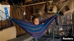 Tina Chakma, a six-month-old baby girl plays in an improvised hammock inside her parents' house on the outskirts of Agartala, India, March 20, 2018.