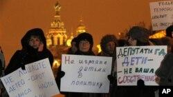 """Para aktivis memegang poster bertuliskan """"Jangan libatkan anak-anak dalam politik"""" dan """"Pembuat hukum, anak-anak bukan milikmu"""" dalam protes di St. Petersburg (26/12) atas RUU yang melarang warga AS mengadopsi anak Rusia. (AP/Dmitry Lovetsky)"""