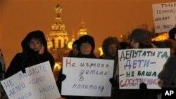 Các nhà hoạt động cầm các biểu ngữ kêu gọi đừng đưa trẻ em vào vấn đề chính trị, trong cuộc biểu tình phản đối luật cấm người Mỹ nhận con nuôi người Nga