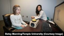 Temple University graduate student Zoe Ngo tests a young student for school's memory study.