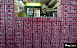 FILE - Crates of Coca-Cola are seen stacked outside a counter of a coffee shop in Singapore, March 14, 2013.