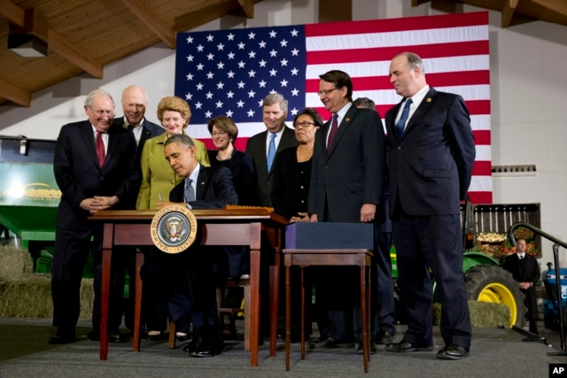 President Barack Obama, surrounded by members of Congress, signs the Farm Bill, Feb. 7, 2014, at Michigan State University in East Lansing, Michigan.