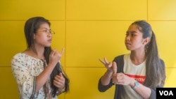 Seng Theary (left) talk to her colleague, Koy Socheata, who has a hearing disability, using sign language at their workplace, Socials Coffee, in Phnom Penh, Cambodia, May 23, 2020. (Hean Socheata/VOA Khmer)