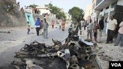 Beberapa warga Somalia melihat rongsokan mobil yang digunakan untuk melakukan serangan bunuh diri di Mogadishu (8/2).