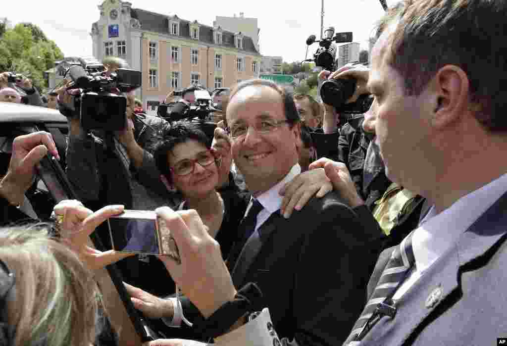 Socialist Party candidate for the presidential election Francois Hollande poses with residents after visiting a polling station near Tulle, central France, May 6, 2012. (AP)