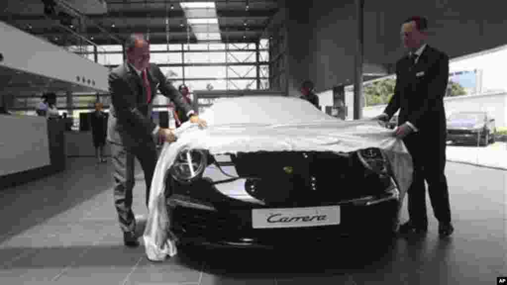 Officials uncover a new Porsche Carrera 911 at a showroom for the luxury brand in Lagos, Nigeria.