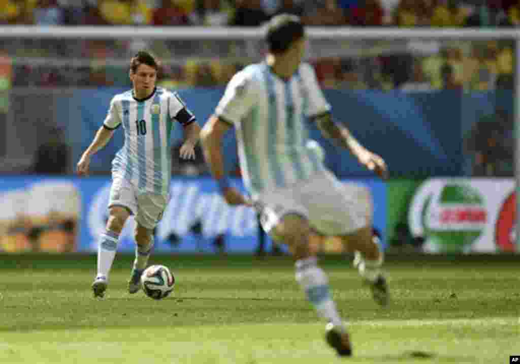 Argentina's Lionel Messi, left, runzs with the ball during the World Cup quarterfinal soccer match between Argentina and Belgium at the Estadio Nacional in Brasilia, Brazil, Saturday, July 5, 2014. (AP Photo/Martin Meissner)