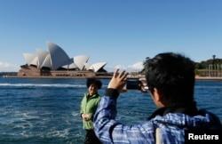 Một du khách Trung Quốc chụp ảnh trước Nhà hát Sydney.