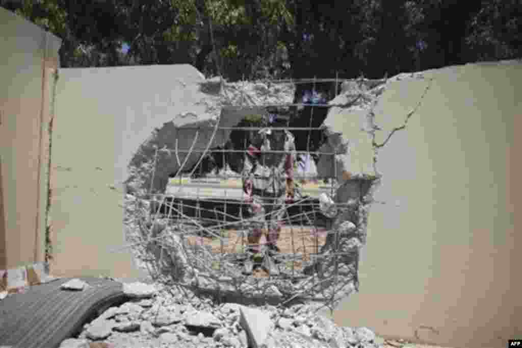 A rebel fighter looks at damages in a house at the town of Brega, Libya, Monday, Aug. 15, 2011. Most of the town has been liberated from Moammar Gadhafi's forces, with fights going on only at the oil terminal, according the rebel military spokesman, Ahmed