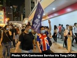 有游行人士身穿印上英国国旗的T恤,高举香港独立旗帜 (美国之音/汤惠芸)