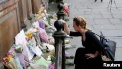 یک زن به یادبود از قربانیان رویداد دوشنبه شب، در مرکز شهر مانچستر دستۀ گل می گذارد.