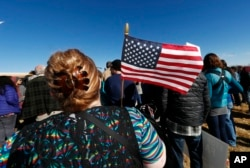 A woman holds an American flag during a rally in support of Jeanette Vizguerra, a Mexican woman seeking to avoid deportation from the United States, outside the Immigration and Customs Enforcement office in Centennial, Colorado, Feb. 15, 2017.