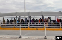 FILE - Migrants from Cuba, Venezuela and Central America queue at the Paso del Norte International Bridge in Ciudad Juarez, Chihuahua state, Mexico, to cross the border and request political asylum in the United States, Jan. 9, 2019.