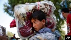 一名加沙少年扛着捐赠毯子和其他离家逃亡的巴勒斯坦难民一道前往一所联合国学校避难。(2014年7月23日)