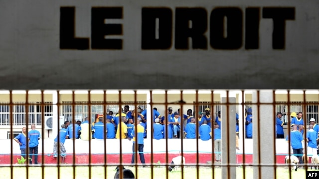 Prisoners are seen at the Makala prison in Kinshasa from behind the bars of the windows of a court room,  on December 18, 2012.